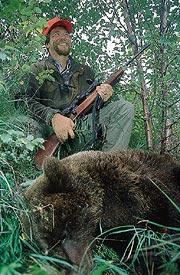 Glad över att ha skjutit sin första björn uppfyller Micke Persson jaktkamraternas begäran att posera vid björnen.