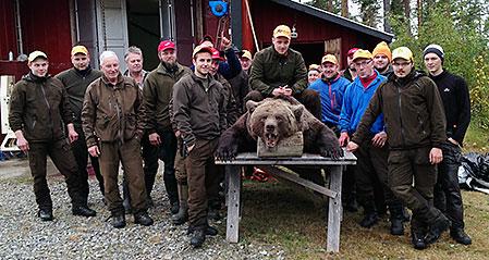 Per Nordwall och jämthunden Hero med sin rekordbjörn omgiven av jägarna i Åkrokens jaktlag.