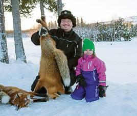 Peter Nilsson och hans dotter Tilda med några av de första rävarna för säsongen 2012/13. teln syns i kanten av ön till höger om Tildas mössa och utgörs av en  björndödad älg.