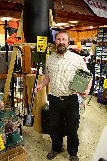 Teknikansvarige Fredrik Lüdecke visar stolt upp nya foderspridaren som vildsvinen själva utlöser med en pendel.