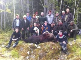 Hela jaktlaget är samlade runt björnhannen som fälldes efter flera timmars jakt.