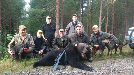 Röste jaktlag med den björn de fällde i lördags morse efter ett bra jobb av Emil Dahls plottik Stinta (tv), som nu står bakom totalt åtta björnar på egen hand.