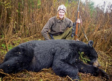Erika Bergmark, med en svartbjörn hon fällde när hon spenderade en höst i Kanada som jaktguide. Foto: Privat