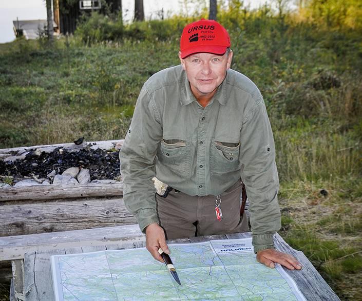 Anders Lindqvist i planerartagen inför en björnjakt, i bakgrunden ser man Holmens bastu vid kanten av Våndtjärn där en av bolagets jaktstugor finns.